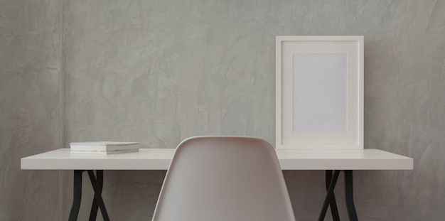 Zolderwerkplaats met wit houten bureau en modelkader en wit boek in grijze muur