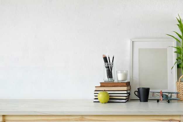 Zolderworkspace met lege affiche op wit houten bureau.