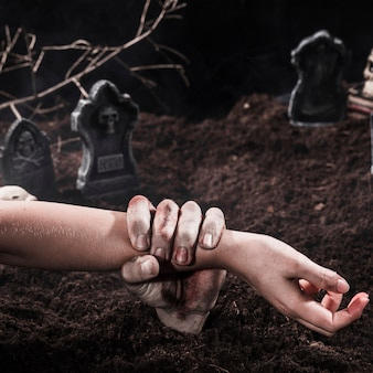 Zombie hand met persoon arm op halloween kerkhof