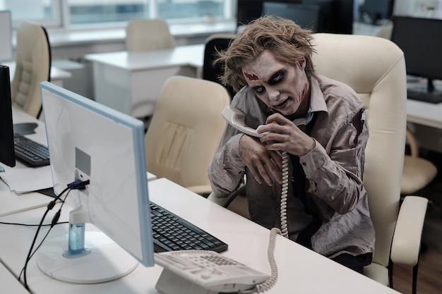 Zombie man met grijze greesepaint over het hele lichaam gaat telefoneren
