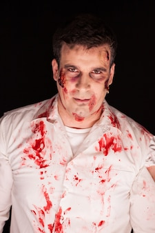 Zombie met bloed op hem na een moord op zwarte achtergrond. spookachtige man.