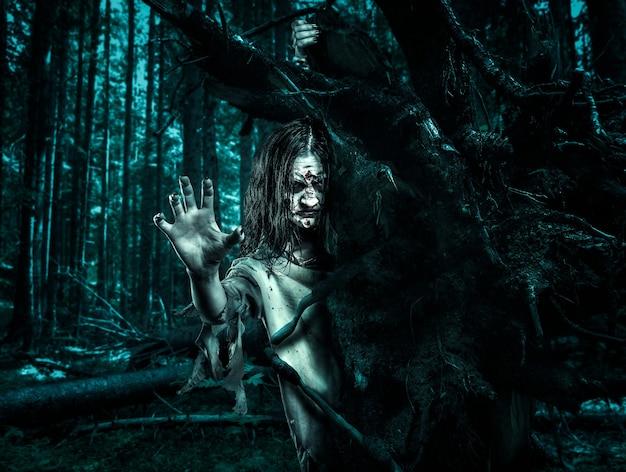 Zombie vrouw in een vuile kamerjas kijkt uit van achter een boom. halloween.