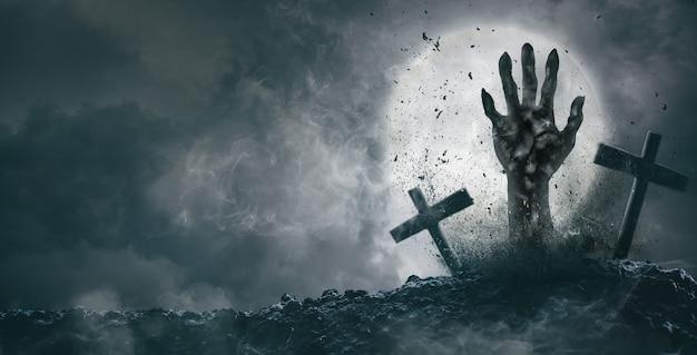 Zombiehand kwam uit het kerkhof op een volle maannacht. halloween-concept
