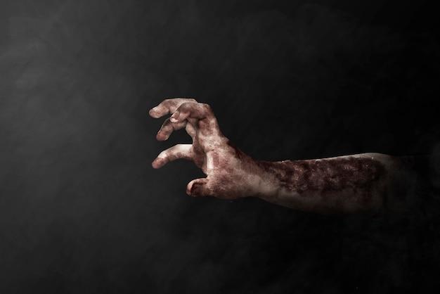 Zombiehand met bloed en wond met zwarte achtergrond