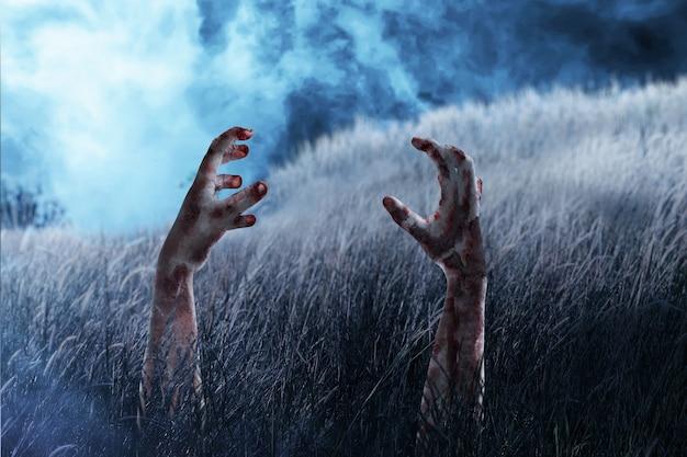 Zombiehand met bloed en wond op de weide