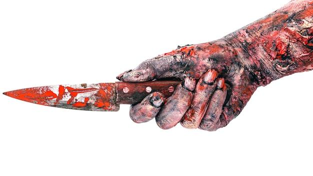 Zombiehand met mes, moordenaarshand bedekt met bloedaanvallend, geïsoleerd wit oppervlak.