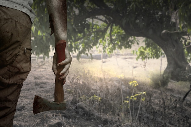 Zombiehanden met wond die een bijl in een spookbos houden