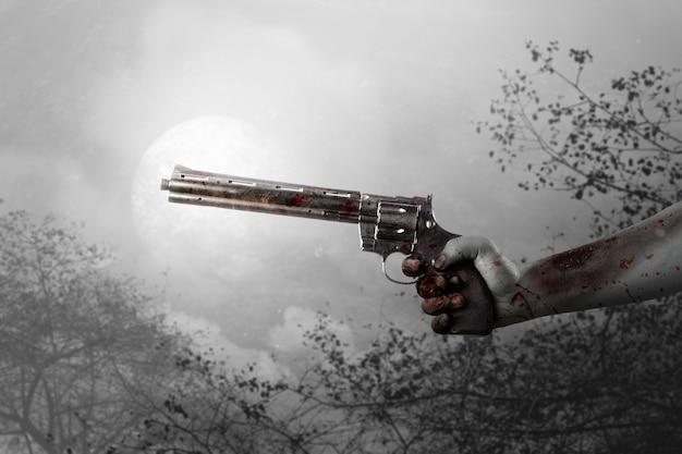 Zombiehanden met wond die een pistool met de achtergrond van de nachtscène houden