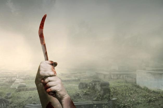 Zombiehanden met wond die sikkel op de begraafplaats houden