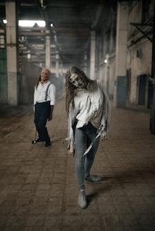 Zombieleger op zoek naar vers vlees, ondode mensen in verlaten fabriek, enge plek. horror in de stad, griezelige kruipers vallen aan, doomsday apocalyps, bloedige kwaadaardige monsters