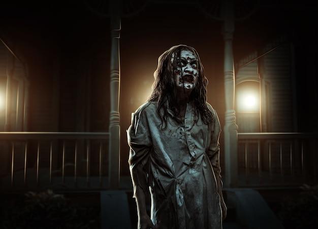 Zombiemeisje dichtbij het verlaten huis. verschrikking. halloween
