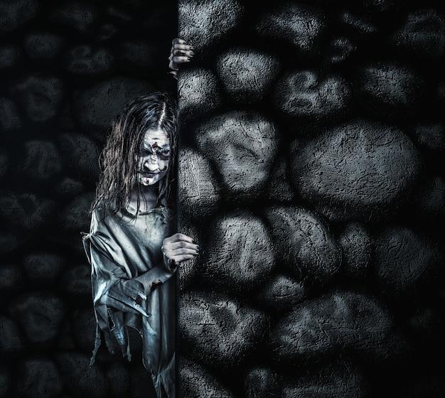 Zombievrouw in vuile kamerjas kijkt uit vanaf de muur