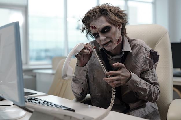 Zombiezakenman met telefoonontvanger die voor computer zit