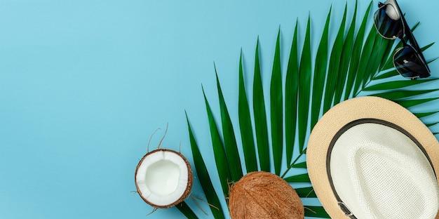 Zomer achtergrond concept. hoed, zonnebril en kokosnoot op blauwe achtergrond. plat leggen, ruimte kopiëren.