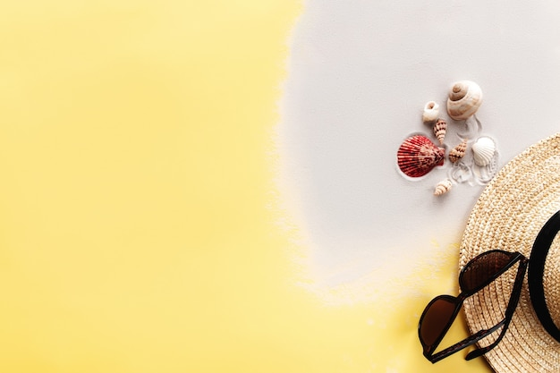 Zomer achtergrond conceptuele plat lag met zand, schelpen, stro hoed en zonnebril op gele achtergrond. hoge kwaliteit foto
