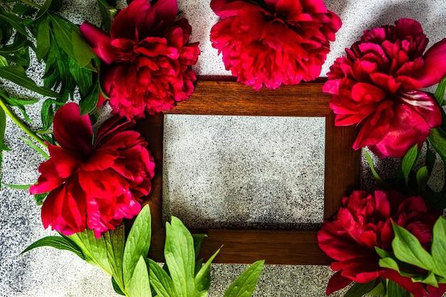 Zomer achtergrond frame met heldere rode pioenroos bloemen op betonnen tafel