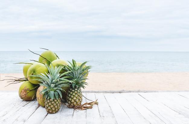 Zomer achtergrond kokosnoten en ananas op witte houten tafel op het strand in de zomer
