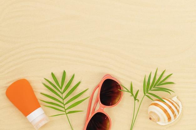 Zomer achtergrond met accessoires op het strand zonnebril zonnebrandcrème zeeschelp en groene bladeren