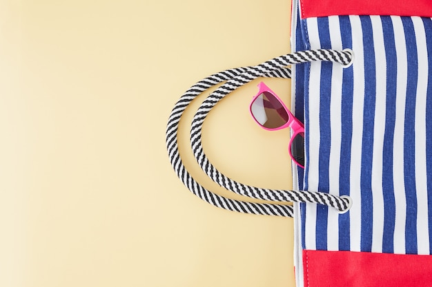 Zomer achtergrond met stro strandhoed, zonnebril, tas en slippers. zomer reizen concept.