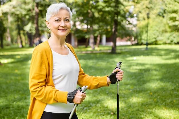Zomer, actieve levensstijl, vrije tijd en hobbyconcept. buiten schot van gezonde energieke bejaarde vrouw in geel vest wandelen in het park op zonnige dag met behulp van noordse stokken, gelukkig kijken