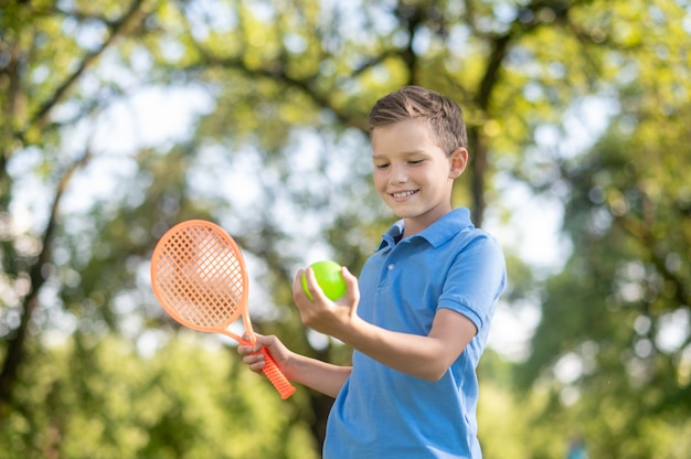 Zomer activiteit. glimlachende blonde jongen met racket die op mooie dag zelfverzekerd naar de tennisbal in de hand kijkt