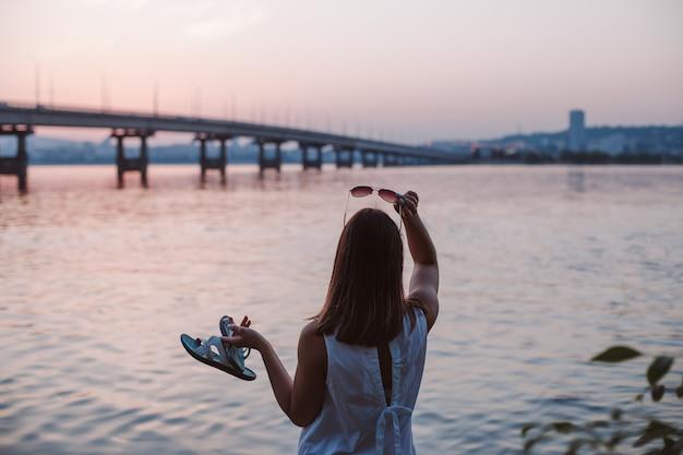 Zomer ansichtkaart een jonge vrouw staat met haar rug met een zonnebril en strandslippers en bewondert de...