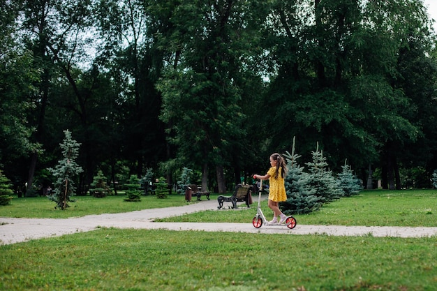 Zomer ansichtkaart een meisje rijdt op een scooter in een groen zomerpark met bomen en een groen gazon op de ach...