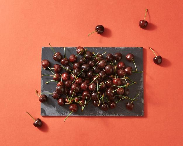 Zomer bessen achtergrond van rode rijpe kersen op donkere stenen bord
