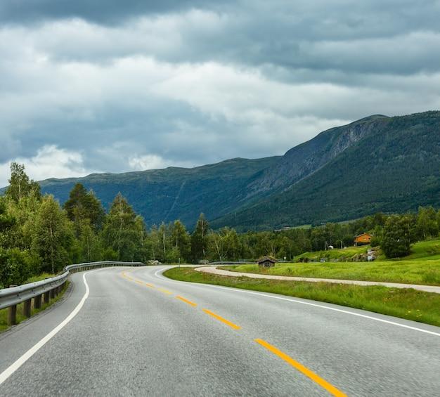 Zomer bewolkt berglandschap met kronkelige secundaire weg, noorwegen