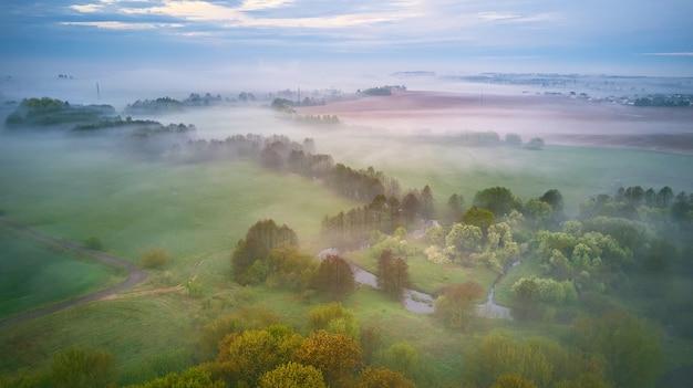 Zomer bewolkt regenachtig mistig ochtendpanorama. landelijke mistige rivier, velden, weide, dorp. lente bewolkt humeurig weer. bloeiende bomen en struiken. wit-rusland, regio minsk