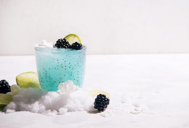 Zomer blauwe cocktail met ijs en bosbessen op een witte achtergrond. ruimte kopiëren