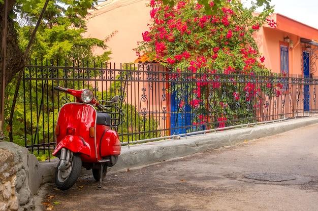 Zomer bloeiende tuin bij zonnig weer. rode scooter in retrostijl staat geparkeerd bij het hek