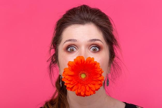 Zomer, bloemen, grappig en mensen concept - vrouw met plezier met gerbera's over het roze oppervlak