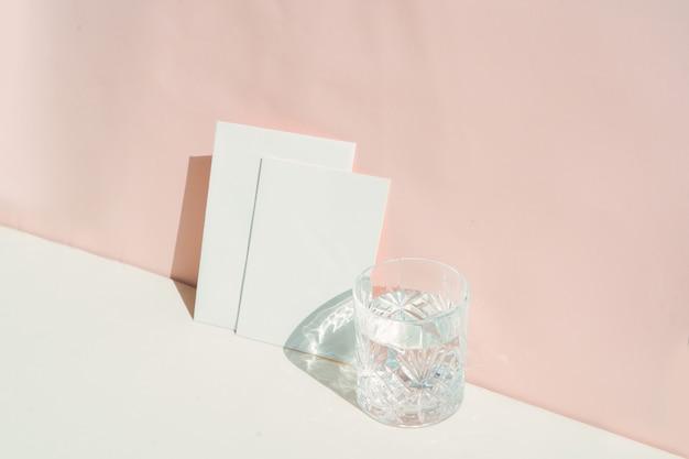 Zomer briefpapier mock-up scène. blanco visitekaartje en glas helder water op beige getextureerde tafelachtergrond