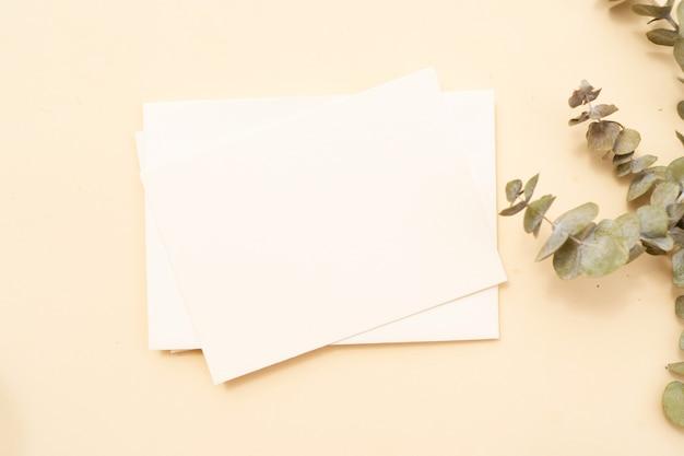 Zomer briefpapier mock-up scène. blanco visitekaartje, groene eucaliptusbladeren, beige getextureerde tabelachtergrond. platliggend, bovenaanzicht