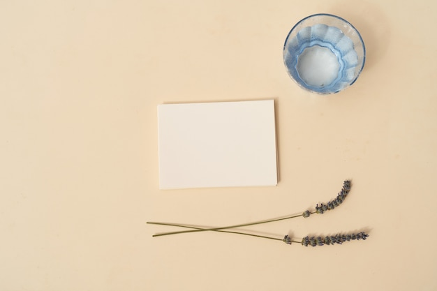 Zomer briefpapier mock-up scène. leeg visitekaartje met lavendelbloemen en glas water op beige getextureerde tabelachtergrond. platliggend, bovenaanzicht
