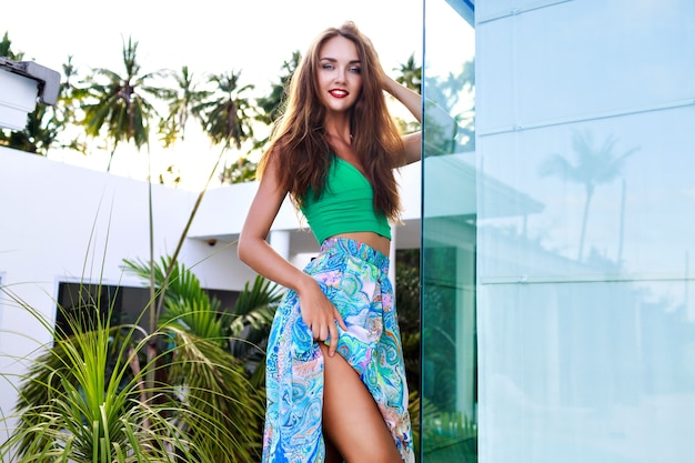 Zomer buiten mode portret van prachtige brunette vrouw met lange haren en lichte make-up, sexy zijden jurk dragen, poseren in luxevilla, avondzonlicht