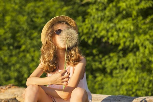 Zomer buiten portret van romantisch meisje in hoed met grote pluizige paardebloem