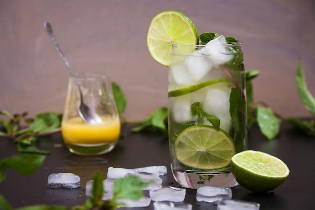 Zomer coctail mojito met ijs, munt, limoen op een grijze achtergrond.