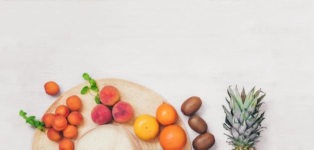 Zomer concept banner vrouwelijke hoed met fruit op houten tafelblad bekijken