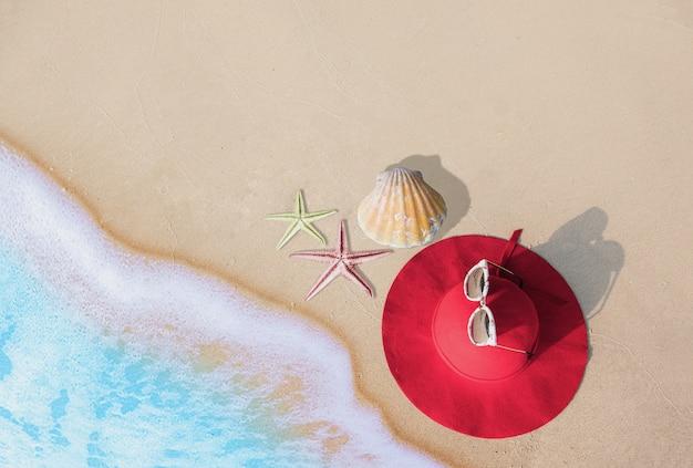 Zomer concept met hoed, zonnebril en schaaldieren op zandstrand. pattaya, thailand.