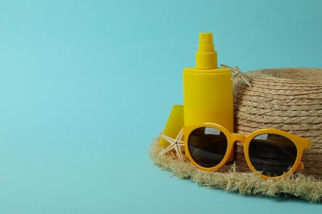 Zomer concept met zonnebrandcrème op blauwe geïsoleerde achtergrond