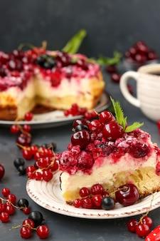 Zomer cottage cheese cake met bessen bevindt zich op een donkere ondergrond, op de voorgrond een fluitje van een cent op een bord, verticale foto