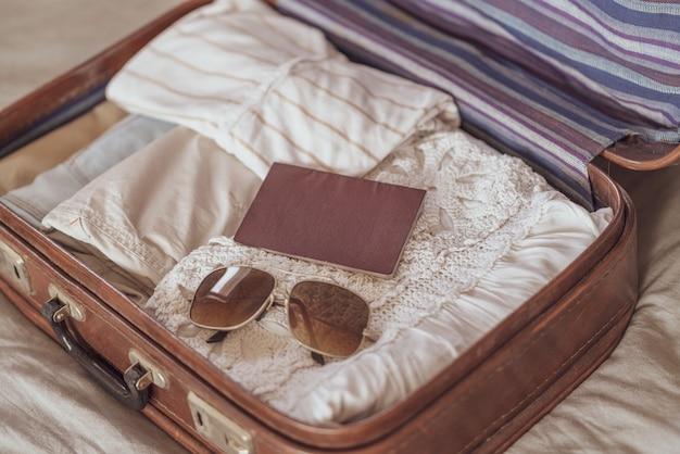 Zomer dameskleding netjes opgevouwen om in een koffer te worden verpakt. reiskoffer voorbereiden.