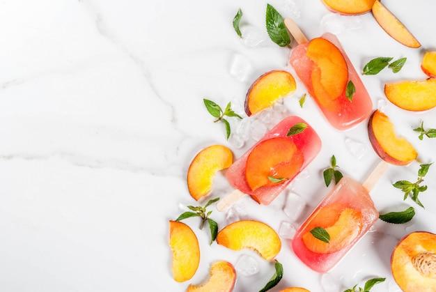 Zomer desserts. bevroren drankjes. zoete fruitijslollys van bevroren perzikthee met munt. op een witte marmeren tafel, met ingrediënten perziken, mint, ijs. copyspace bovenaanzicht