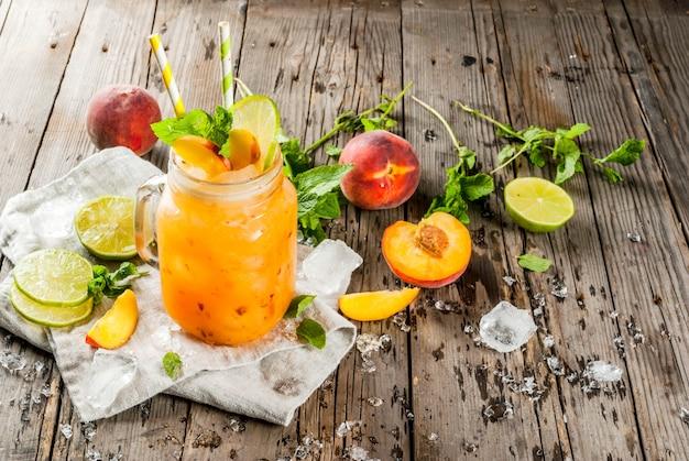 Zomer drankjes, cocktails. veganistisch eten. perzik smoothies, sap of limonade. in een stenen pot, met limoen
