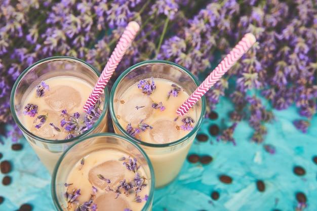 Zomer drink ijskoffie met lavendel in glas en koffiebonen op blauwe tafel.