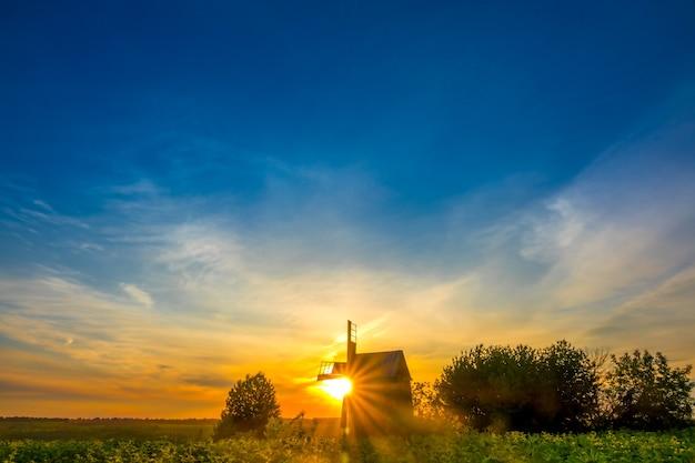Zomer. een oude houten windmolen omringd door zonnebloemen. de zon komt op achter de windmolen en schildert de lucht in prachtige kleuren