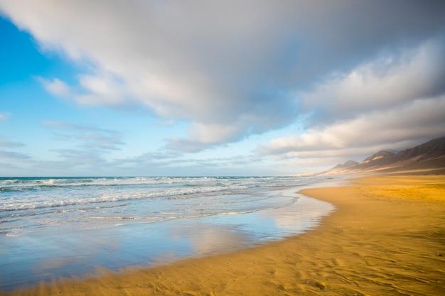 Zomer eenzaam strand met water reflecties concept