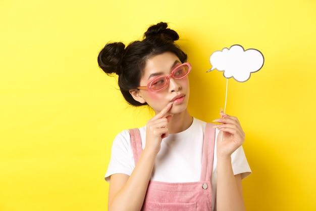 Zomer en mode-concept. stijlvol glamour aziatisch meisje in zonnebril, houdt het partijmasker van de commentaarwolk vast en kijkt opzij, geel